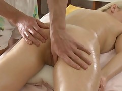 Masseur is soothing beauty's sexy body with oil massage